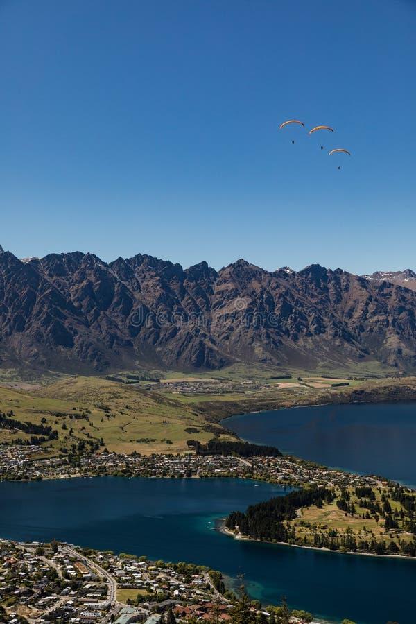 三个滑翔伞鸟瞰图在昆斯敦,新西兰的和瓦卡蒂普湖在蓝天下 免版税库存照片