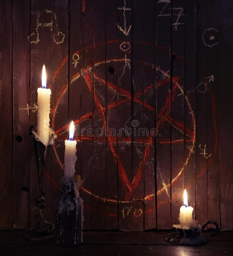 三个灼烧的蜡烛和木板条与五角星形 免版税库存照片