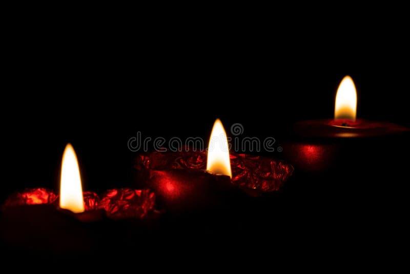 三个燃烧的红色蜡烛行的特写镜头在黑暗的与a 图库摄影
