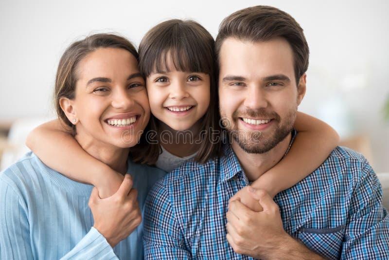三个爸爸妈妈和小的女儿画象幸福家庭  免版税库存图片
