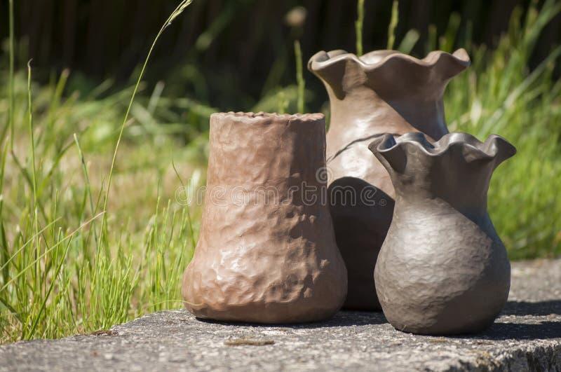 三个独特的手工制造花瓶特写镜头陶瓷在夏天阳光下 免版税库存照片
