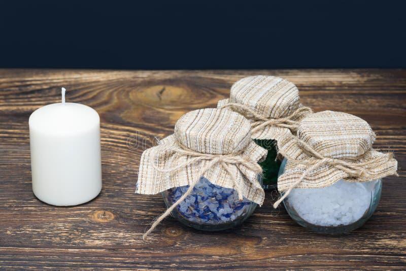 三个瓶在一张桌上的海盐与一个蜡烛 免版税库存图片