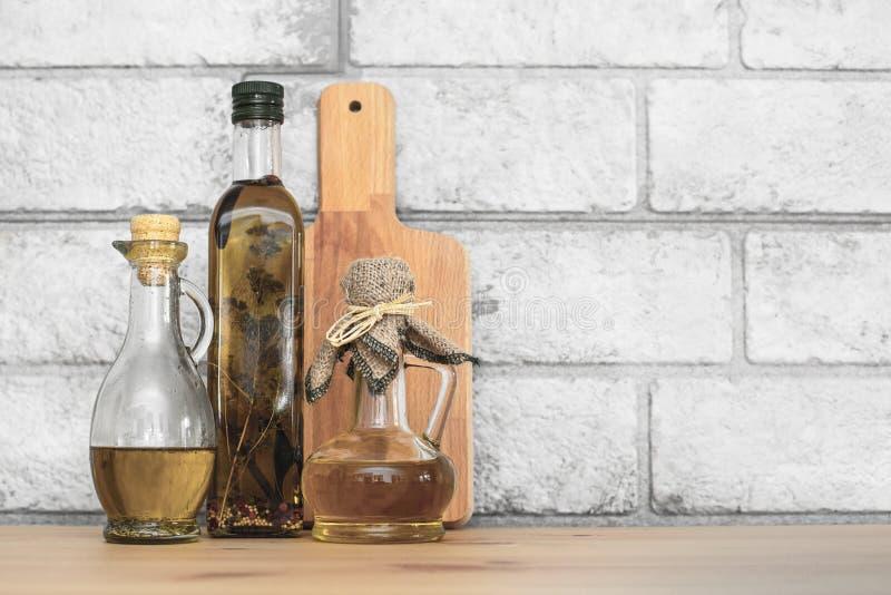 三个瓶在灰色砖背景的橄榄油 库存图片