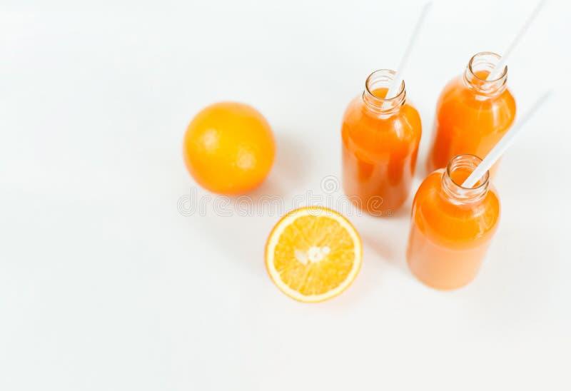三个瓶橙汁和管在白色背景的桌上 库存图片