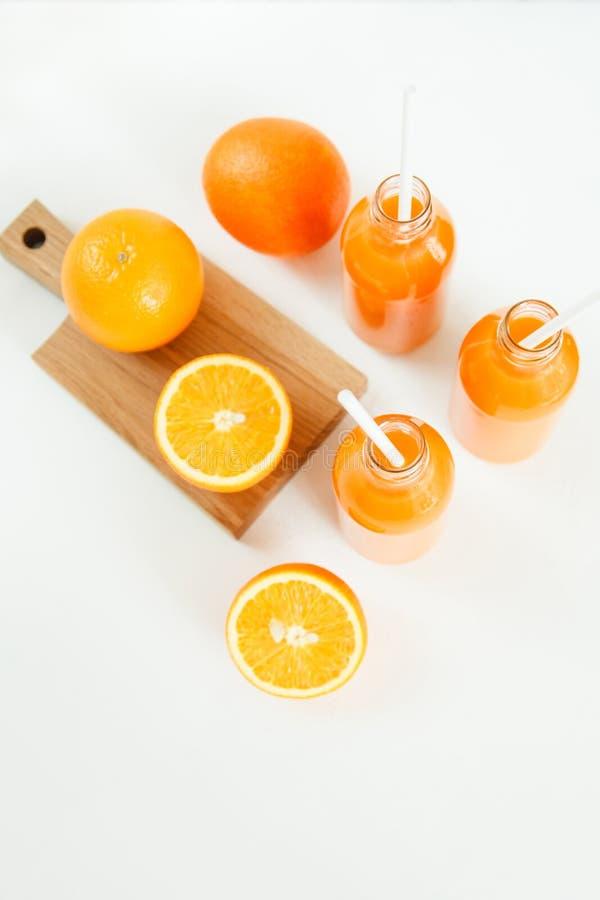 三个瓶橙色新鲜和管在桌上 库存照片