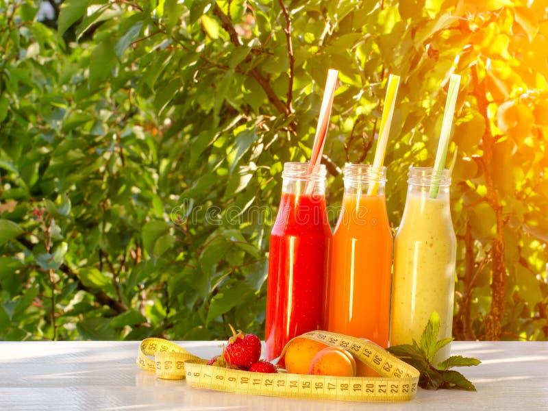 三个瓶汁液、果子和测量的磁带在绿色背景,食物概念 免版税库存照片