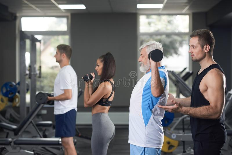 三个男人和妇女每日训练的在健身房 库存照片