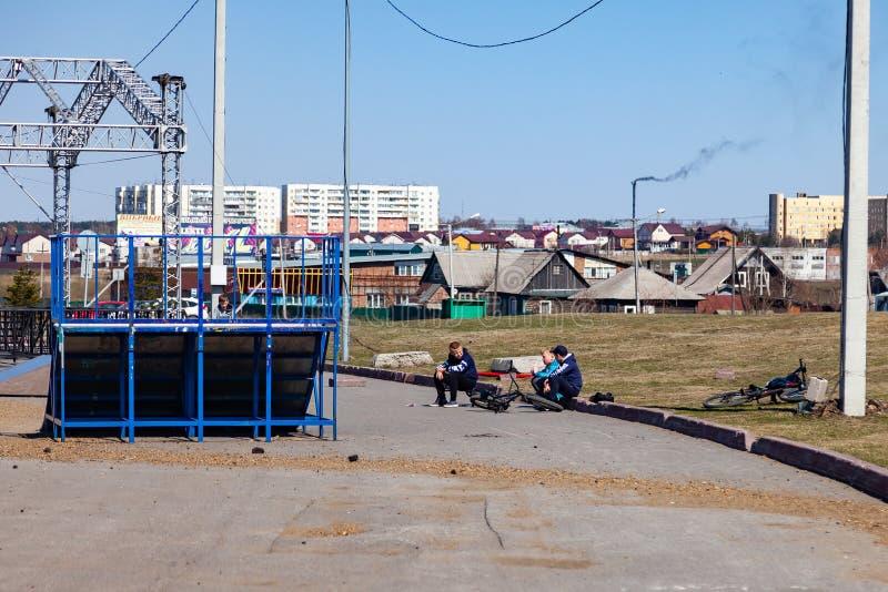 三个男孩一坐草坪,当休息时在骑BMX的自行车以后在舷梯附近执行把戏,谈论某事之间 免版税库存照片