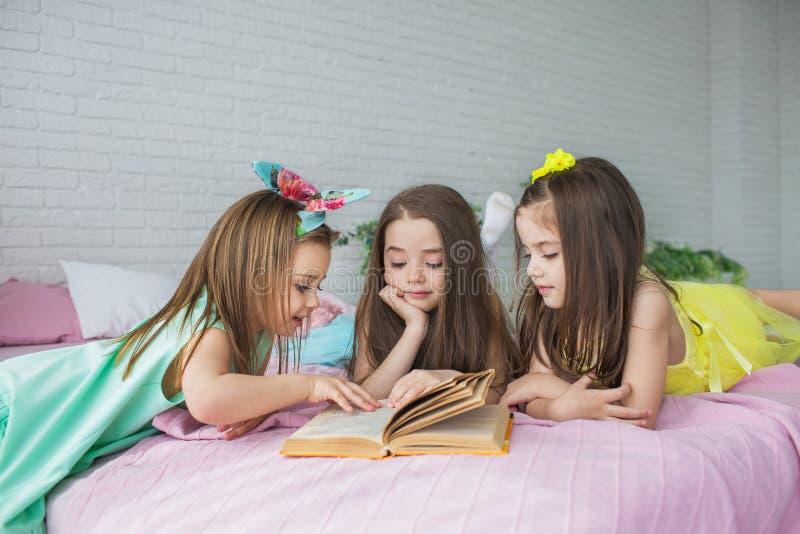 三个相当小女孩在床上躺并且看书 库存图片