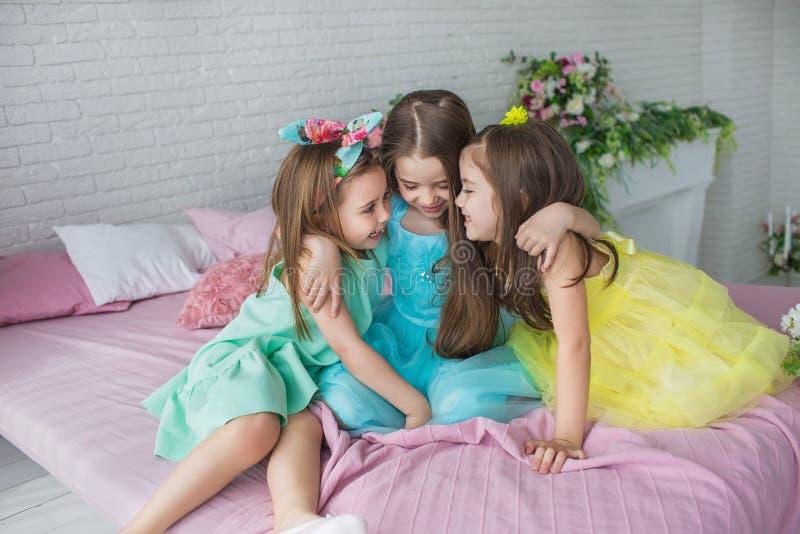 三个相当小女孩坐床并且互相拥抱 免版税库存照片