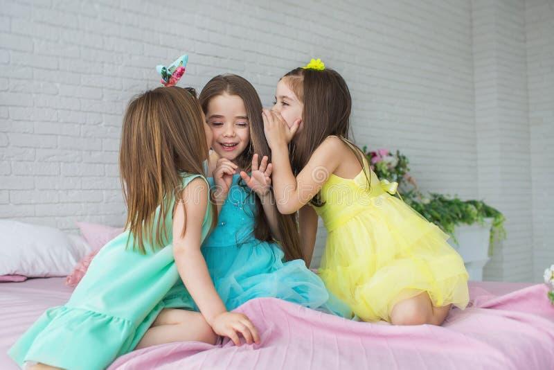 三个相当小女孩坐床并且互相耳语 库存照片