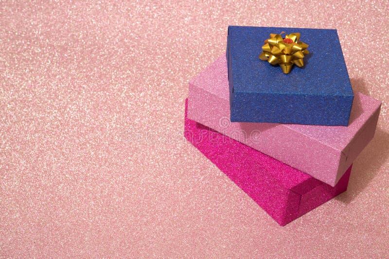 三个礼物盒在桃红色发光的背景站立堆积 库存图片