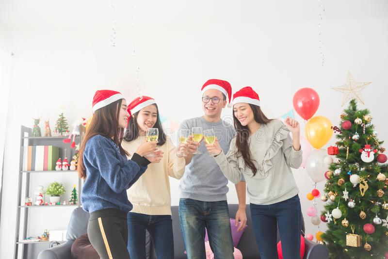 三个美丽的亚裔女孩和庆祝圣诞节用酒的一个人 免版税图库摄影