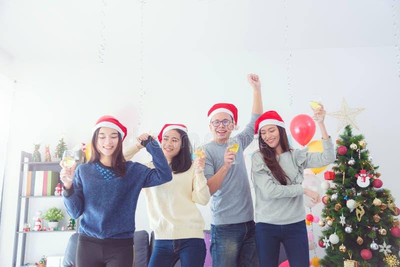三个美丽的亚裔女孩和庆祝圣诞节用酒的一个人 免版税库存图片