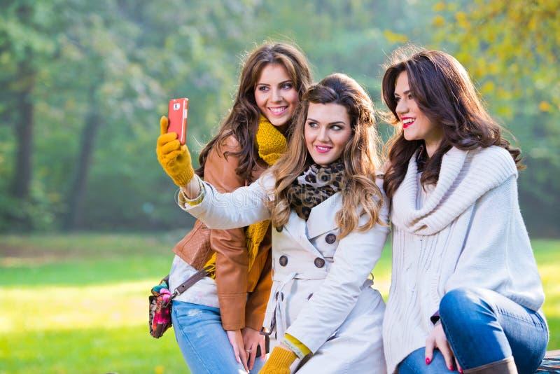 三个美丽的少妇在拍照片的公园 免版税库存照片
