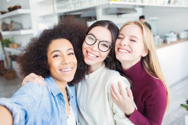 三个美丽的朋友一起采取selfie 有美国黑人的女孩、一个浅黑肤色的男人和一个金发碧眼的女人 他们是 库存照片