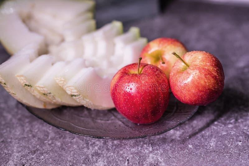 三个美丽的红色苹果和一个瓜在板材 库存图片