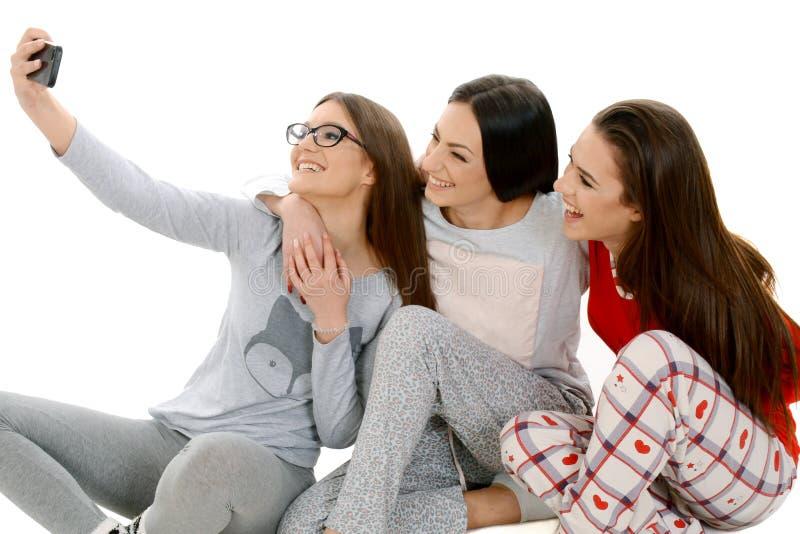 三个美好的愉快的女孩ih他们的采取selfie与的睡衣 库存照片
