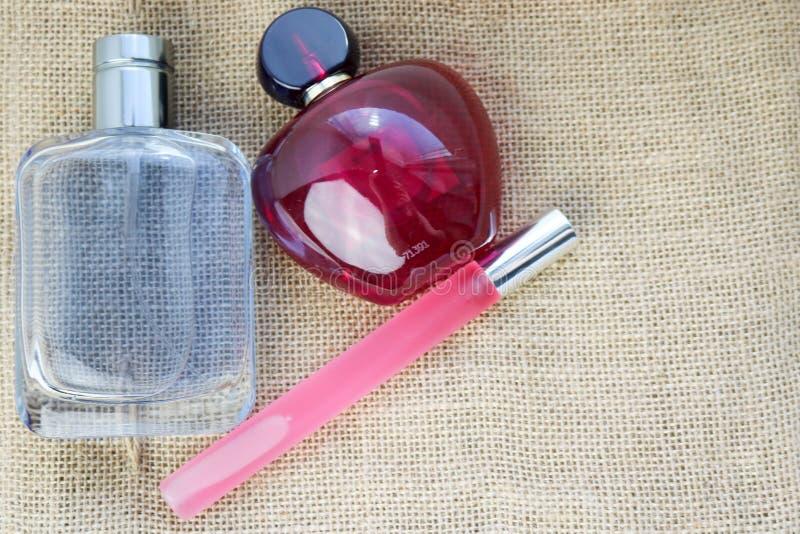 三个美好的玻璃时尚迷人的科隆香水小瓶,充满香气桃红色亭亭玉立,红色在周围,并且蓝色长方形与小的小珠间隔f 库存照片
