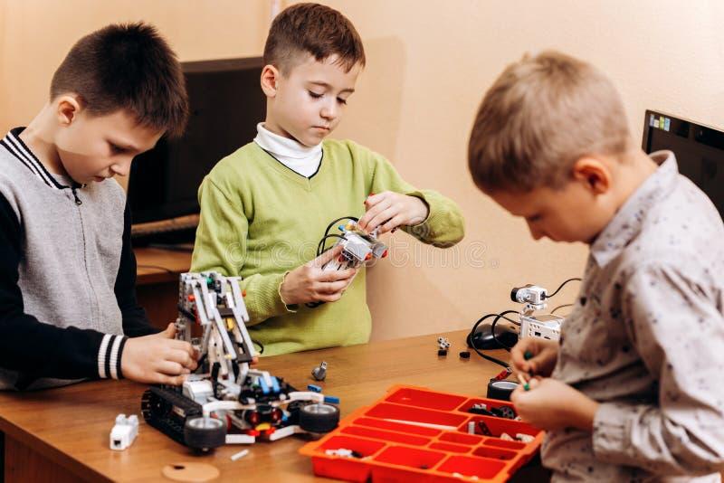 三个聪明的男孩由机器人建设者做机器人在有计算机的书桌在机器人学学校  免版税库存照片