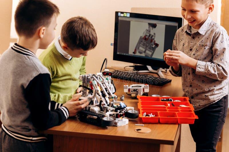 三个聪明的男孩由机器人建设者做机器人在机器人学学校  免版税库存照片