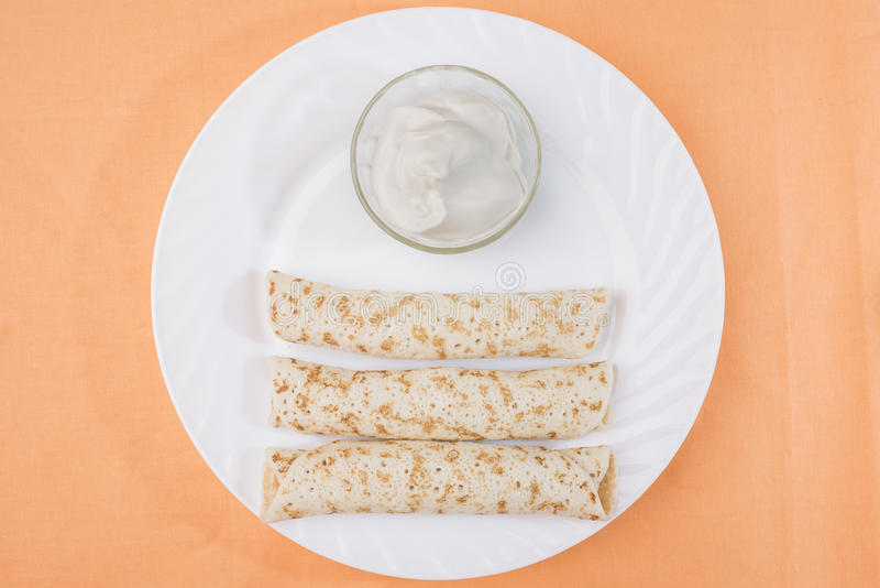 三个薄煎饼滚动与充塞和在一个碗的酸性稀奶油在一块大白色板材 免版税库存照片
