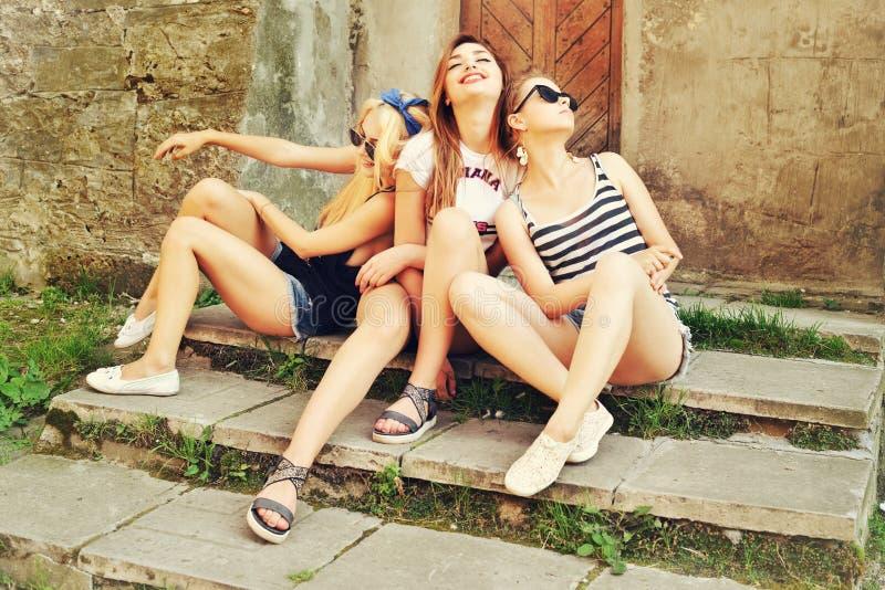 三个街道的美好的女孩基于 太阳镜的美丽的愉快的女孩在都市背景 有效的人年轻人 Outdoo 免版税库存照片