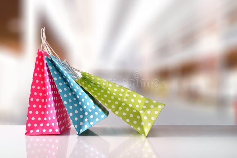 三个袋子上色与在购物中心的白色圈子朝向 免版税库存照片