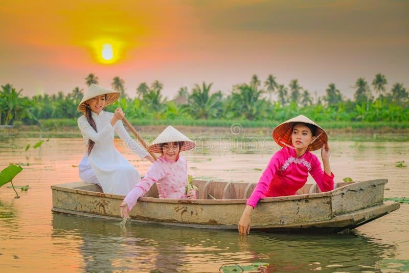 三个越南女孩在莲花庭院里荡桨 免版税库存照片