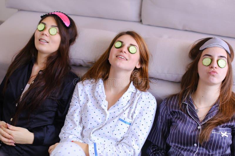 三个迷人的女性朋友放松并且做面部秀丽款待 库存照片