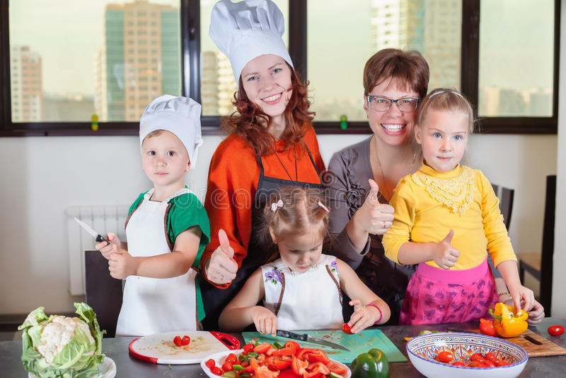 三个逗人喜爱的孩子在厨房里准备沙拉 库存照片