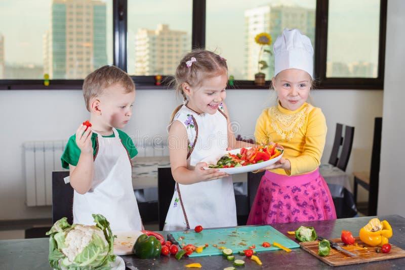 三个逗人喜爱的孩子在厨房里准备沙拉 图库摄影