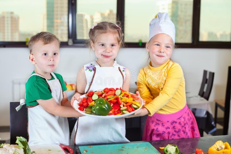 三个逗人喜爱的孩子在厨房里准备沙拉 免版税库存图片