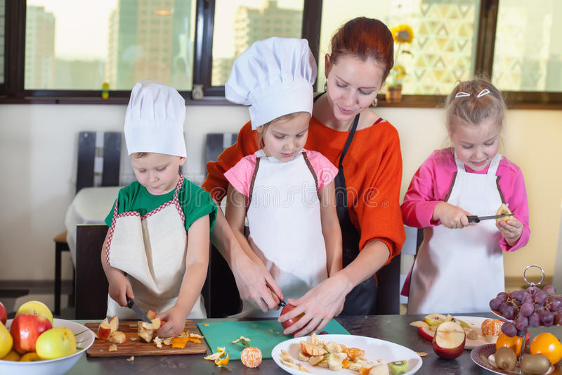 三个逗人喜爱的孩子在厨房里准备水果沙拉 图库摄影