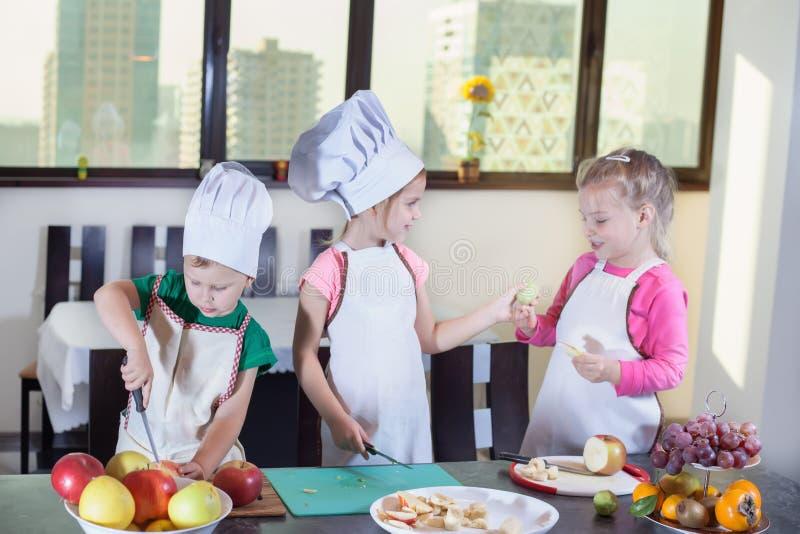 三个逗人喜爱的孩子在厨房里准备水果沙拉 免版税图库摄影
