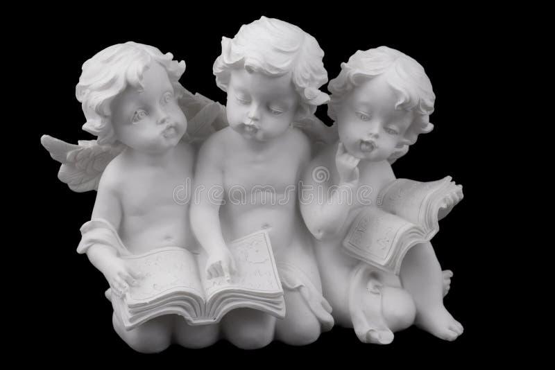 三个陶瓷白色天使读了书,作梦和认为 库存图片