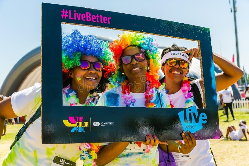 三个非洲女孩获得乐趣在颜色跑5km马拉松,增殖比 免版税库存照片