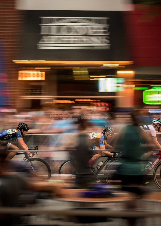 三个骑自行车者仓促通过街市雅典 免版税库存照片