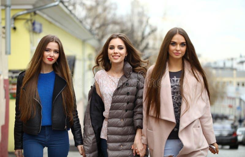 三个年轻美丽的女朋友在秋天给走在t穿衣 免版税图库摄影
