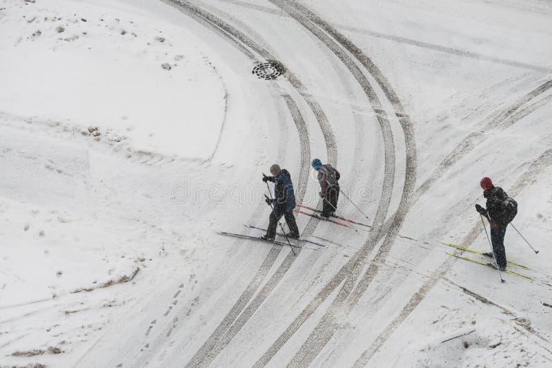 三个滑雪者横渡汽车泥泞的脚印  库存图片
