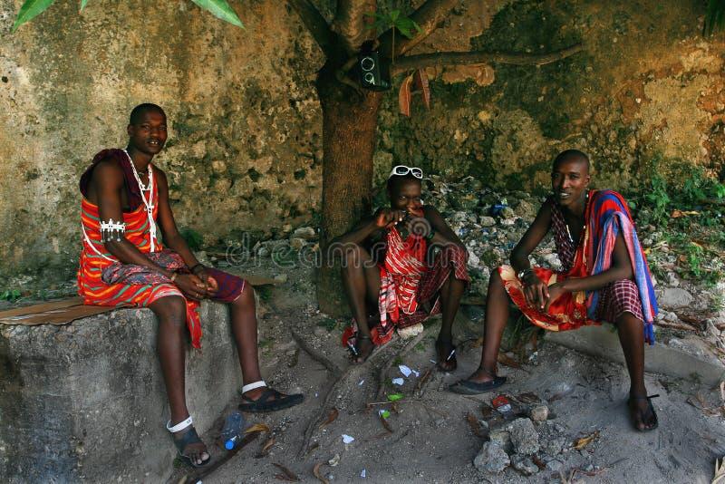 三个年轻非洲人,马塞人衣物,休息在树荫下。 库存图片