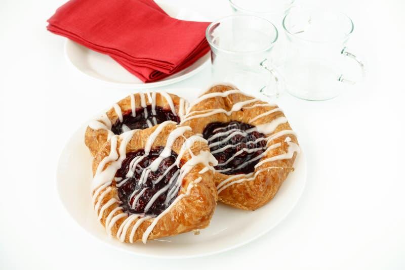 三丹麦樱桃酥皮点心、水杯和餐巾 免版税库存照片