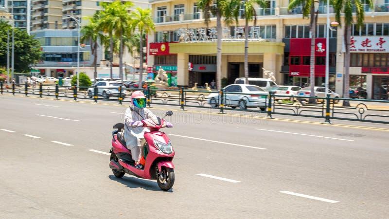 三亚,海南,中国- 2019年5月15日:公路交通 妇女乘坐electromoped的  免版税库存照片
