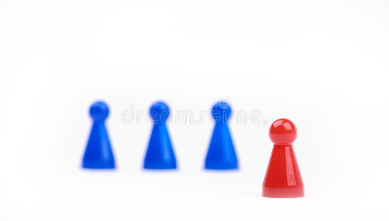 三以一团队弄脏了蓝色比赛片断和一个红色提高的图作为在前景的一位领导 与有选择性的特写镜头照片 免版税库存照片