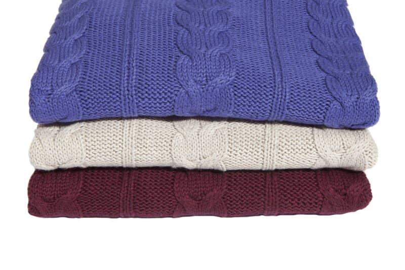 三件被折叠的毛线衣的片段 库存图片