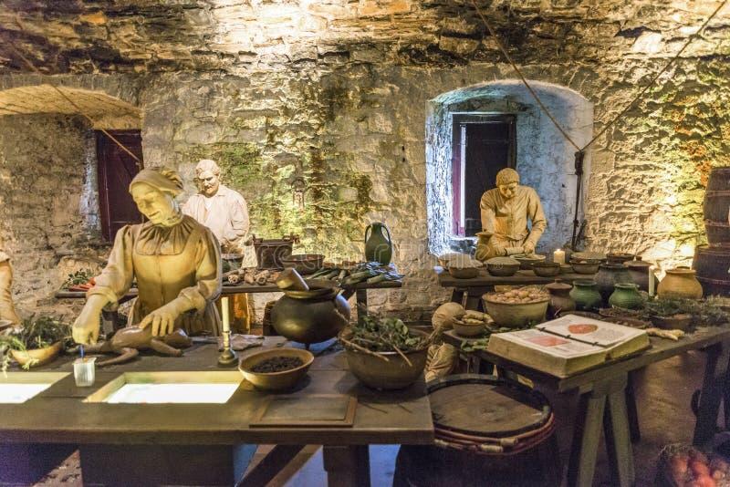 三位厨师成份在伟大的厨房里为下顿膳食,斯特灵城堡做准备 免版税库存照片