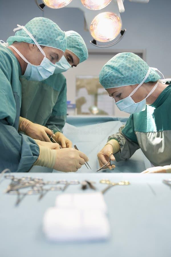 三位外科医生在工作在手术室 库存图片