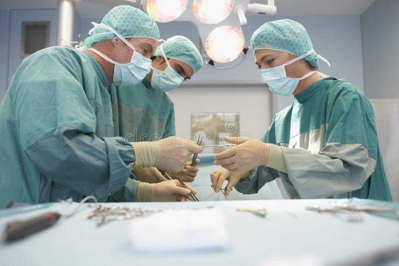 三位外科醫生在工作在手術室圖片