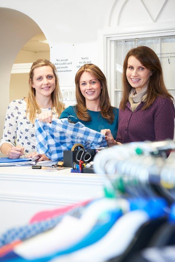 三位女性志愿工作者在慈善商店 免版税库存照片
