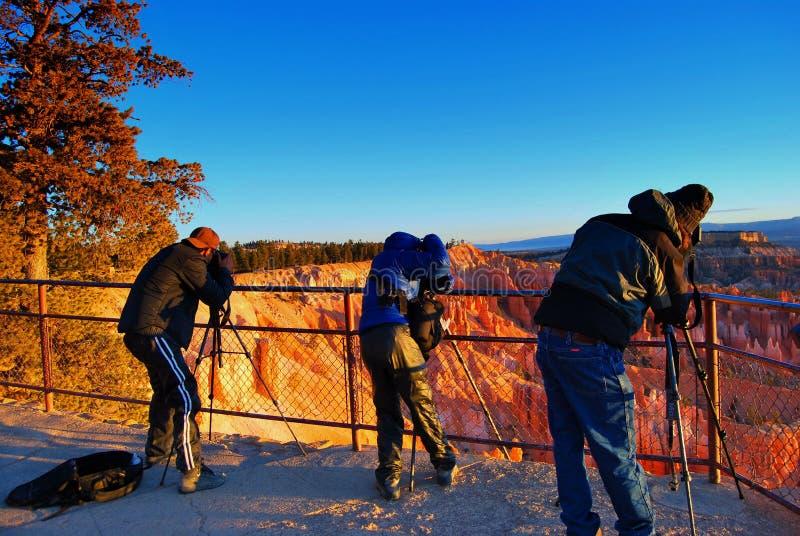 三位摄影师为在bryce峡谷国家公园的日出射击做准备 免版税库存照片